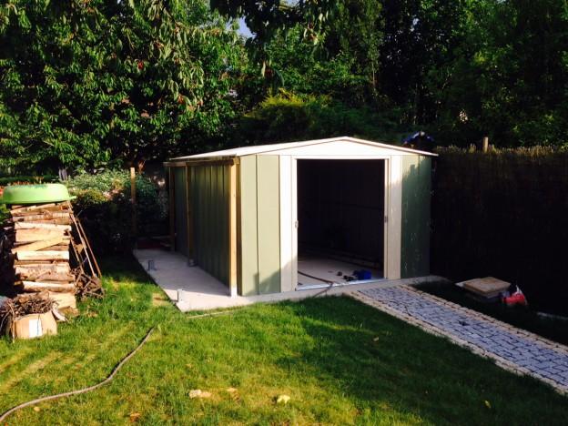 Un abri de jardin en métal vert et crème