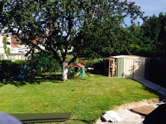 Un abri en métal avec bûcher installé dans le jardin