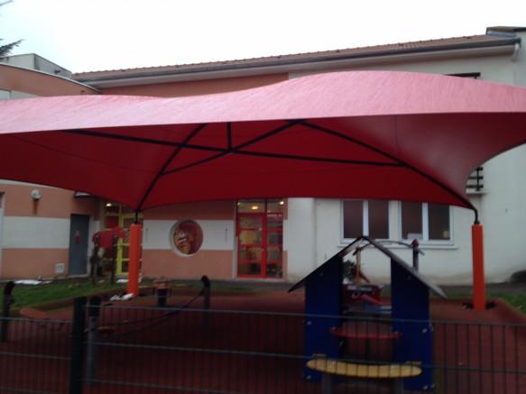 Aire de jeux pour enfants dans établissement scolaire abrité par une toile tendue