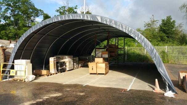 Tunnel de stockage de couleur grise accueillant du matériel BTP