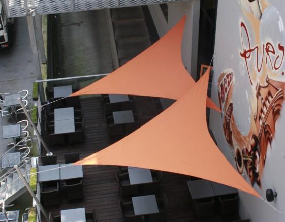 voiles d'ombrage oranges au dessus d'une terrasse de restaurant