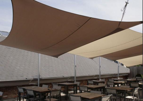 une terrasse de café ombragée grâce à des voiles d'ombrage rectangulaires