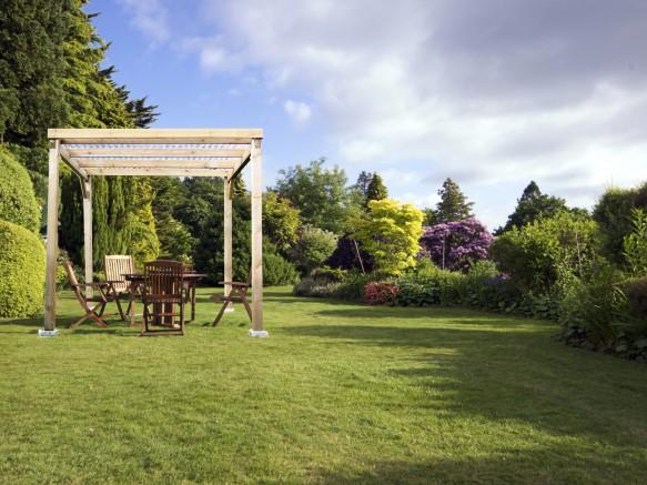 une pergola en bois clair au milieu d'un grand jardin