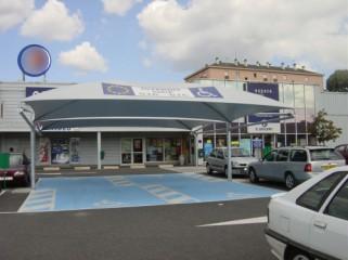 Un grand abri couvrant plusieurs places handicapées sur un parking  de grande surface