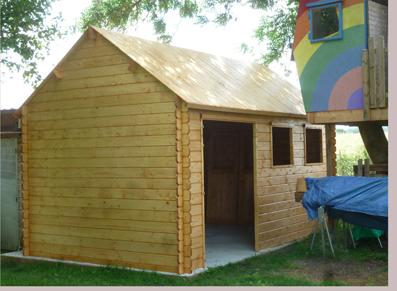 Un abri en bois dans un jardin avec un toit forte pente