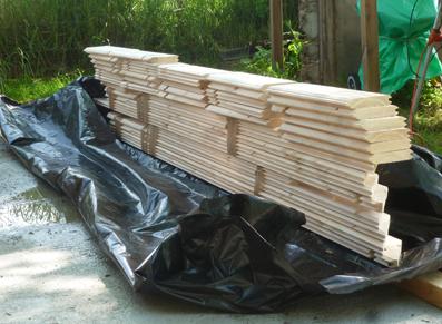 Des planches de bois disposées sur une bâche : la genèse du montage d'un abri de jardin !