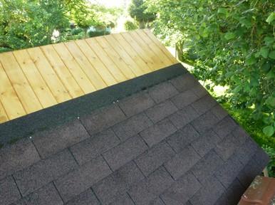 Le toit fortement incliné d'un abri de jardin en bois