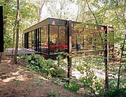 Abri dans la forêt pour servir de garage à voiture tout en verre