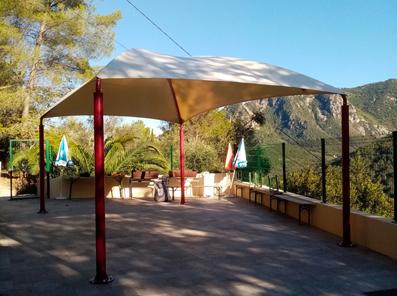 Une toile PVC haute densité et des poteaux métalliques pour abriter les réceptions d'un centre de vacances