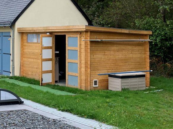 Un abri de jardin en bois à toit plat transformé en pool house
