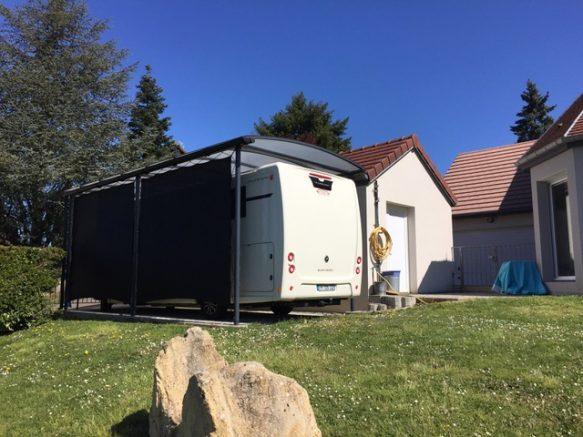 Un abri camping-car avec toit bac acier et une bâche latérale occultante